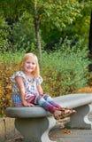Усмехаясь девушка сидя на стенде в парке города Стоковые Изображения