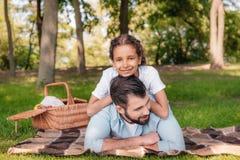 Усмехаясь девушка смотря камеру пока лежащ на отце в парке Стоковая Фотография
