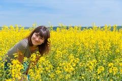 Усмехаясь девушка среди поля желтых цветков Стоковые Фотографии RF