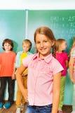 Усмехаясь девушка стоит около зеленого классн классного Стоковая Фотография