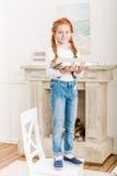 Усмехаясь девушка стоя на стуле и держать книги Стоковая Фотография