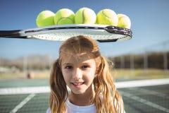 Усмехаясь девушка стоя под ракеткой и шариками тенниса Стоковое фото RF