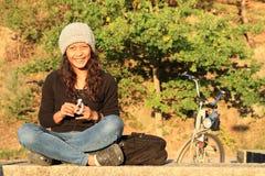 Усмехаясь девушка с велосипедом позади Стоковое Изображение RF