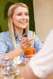 Усмехаясь девушка с коктеилем в кафе Стоковая Фотография RF