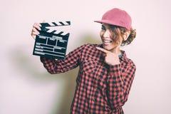 Усмехаясь девушка с колотушкой кино на белой предпосылке Стоковые Изображения