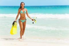 Усмехаясь девушка с ребрами и маска идя на побережье стоковое фото