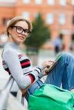 Усмехаясь девушка с таблеткой пешеходного перехода на улице Стоковые Изображения RF