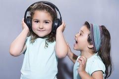 Усмехаясь девушка слушая к музыке в наушниках с близрасположенным сестры кричащее Стоковые Изображения RF