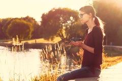Усмехаясь девушка с чашкой чаю или кофе наслаждаясь на лете подпирают стоковое изображение