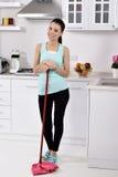 Усмехаясь девушка убирая дом стоковая фотография rf