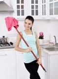 Усмехаясь девушка убирая дом стоковое фото