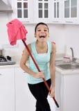 Усмехаясь девушка убирая дом стоковые изображения