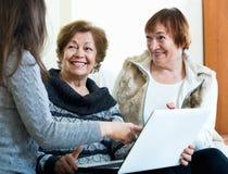 Усмехаясь девушка уча положительным старшим женщинам используя компьтер-книжку Стоковая Фотография RF
