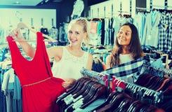 2 усмехаясь девушки выбирая платье совместно Стоковые Фото