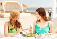 Усмехаясь девушки в кафе на пляже Стоковое Изображение RF