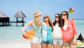 Усмехаясь девушки в тенях имея потеху на пляже Стоковое Фото
