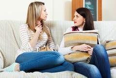 Усмехаясь девушки говоря на софе Стоковое фото RF