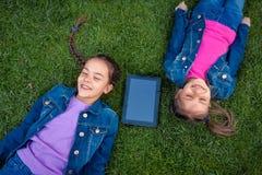 Усмехаясь девушки лежа на траве с цифровой таблеткой Стоковое Изображение