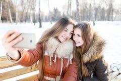 2 усмехаясь девушки делают selfie в парке зимы Стоковая Фотография