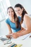 Усмехаясь девушки делая домашнюю работу дома Стоковое Фото
