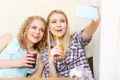 2 усмехаясь девушки делая selfie в кафе Стоковая Фотография RF