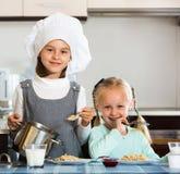 2 усмехаясь девушки имея завтрак с кашой овсяной каши Стоковая Фотография RF