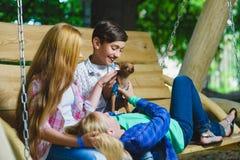Усмехаясь девушки и мальчик имея потеху на спортивной площадке Дети играя outdoors в лете Подростки на качании Стоковая Фотография RF