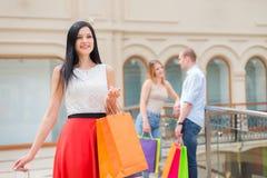 Усмехаясь девушки и человек с хозяйственными сумками в роскошном центральном магазине Покупки, продажа, подарки и концепции празд Стоковое Фото