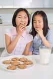 2 усмехаясь девушки наслаждаясь печеньями и молоком в кухне Стоковое фото RF