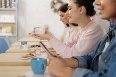 Усмехаясь девушки отдыхая в кафе Стоковое Изображение RF