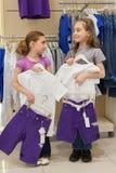 2 усмехаясь девушки пробуя на таком же платье в магазине Стоковая Фотография RF