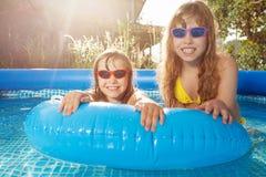 Усмехаясь девушки плавая в бассейне с резиновым кольцом Стоковые Фото