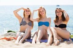 Усмехаясь девушки сидя на пляже Стоковая Фотография RF