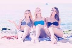 Усмехаясь девушки сидя на пляже Стоковое Изображение
