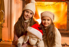 2 усмехаясь девушки сидя рядом с камином и играя с игрушкой Стоковое Изображение