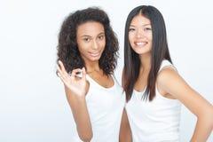 Усмехаясь девушки скрепляя друг к другу Стоковое Изображение