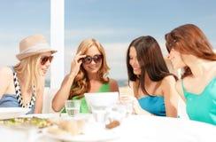 Усмехаясь девушки смотря ПК таблетки в кафе Стоковая Фотография