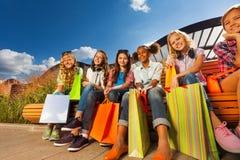 Усмехаясь девушки с хозяйственными сумками сидят в строке Стоковое фото RF