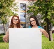 2 усмехаясь девушки с eyeglasses и пустой доска Стоковая Фотография RF