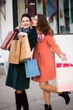 Усмехаясь девушки шепча пока ходящ по магазинам Стоковые Изображения RF