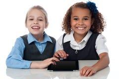 Усмехаясь девушки школы играя на сенсорной панели Стоковая Фотография
