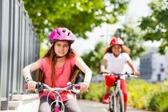 Усмехаясь девушки preteen ехать велосипед в парке города Стоковая Фотография
