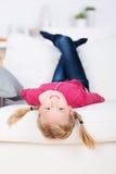 Усмехаясь лежать девушки вверх ногами на софе Стоковое Изображение