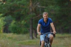 Усмехаясь езды велосипедиста на велосипеде в сосновом лесе Стоковая Фотография RF