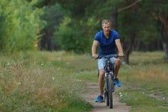 Усмехаясь езды велосипедиста на велосипеде в сосновом лесе Стоковые Изображения RF