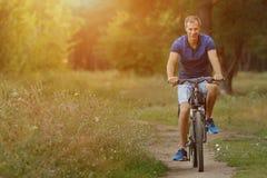 Усмехаясь езды велосипедиста на велосипеде в сосновом лесе Стоковое фото RF