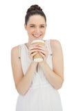 Усмехаясь естественная модель в кофе белого платья выпивая стоковое фото