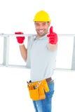 Усмехаясь лестница нося разнорабочего пока показывающ жестами большие пальцы руки вверх Стоковое фото RF