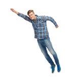 Усмехаясь летание молодого человека в воздухе стоковое фото rf