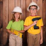 Усмехаясь дети в защитных шлемах с инструментами конструкции на деревянном Стоковое фото RF